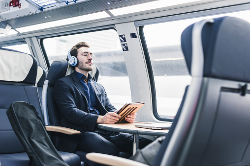 Businessman in train relaxing listening to music - gettyimageskorea