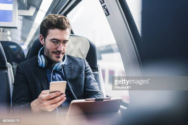 businessman in train with cell phone, headphones and tablet - draagbare informatie apparatuur stockfoto's en -beelden
