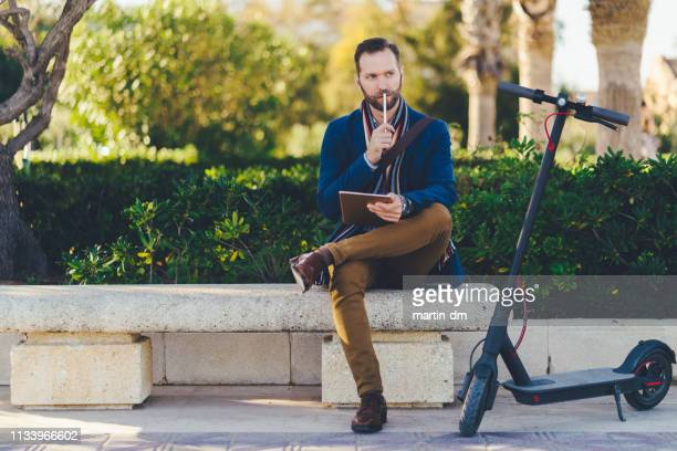 businessman in valencia using tablet in the park - motor scooter stock pictures, royalty-free photos & images
