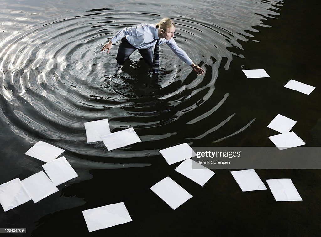Businessman in water gathering floating paperwork : Stock Photo