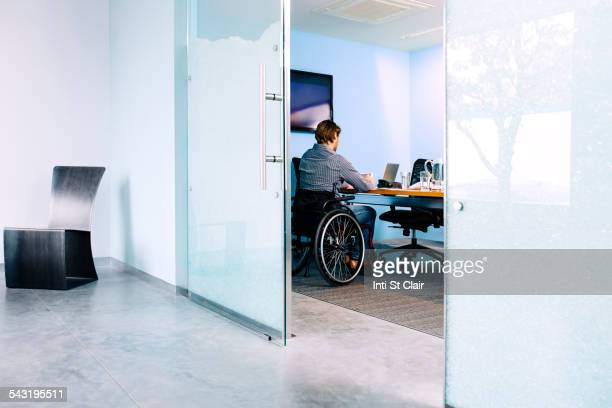Businessman in wheelchair working at desk in office
