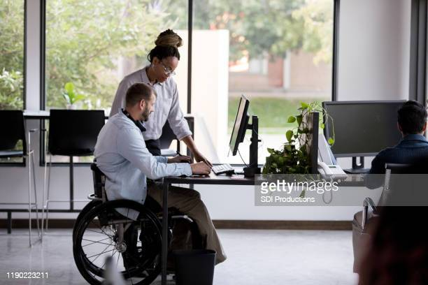 businessman in wheelchair works with female colleague - disabilitycollection stock pictures, royalty-free photos & images