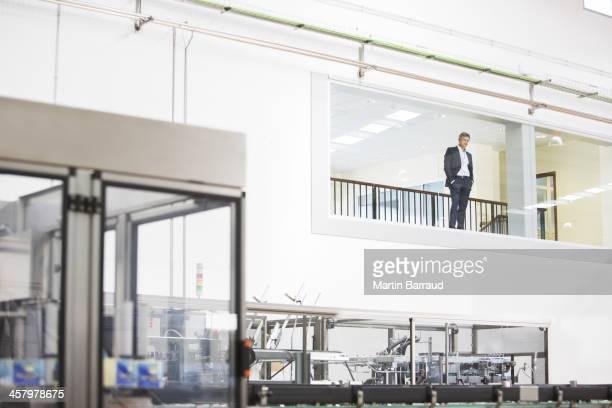 Businessman in window overlooking factory