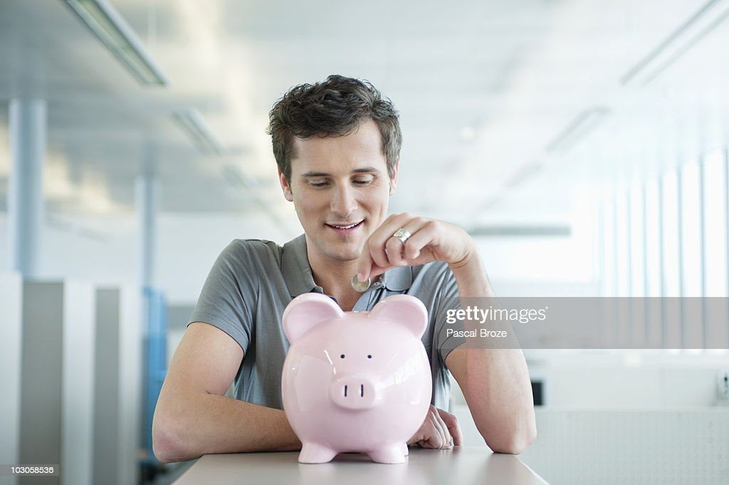 Businessman inserting a coin into a piggy bank : Stock Photo