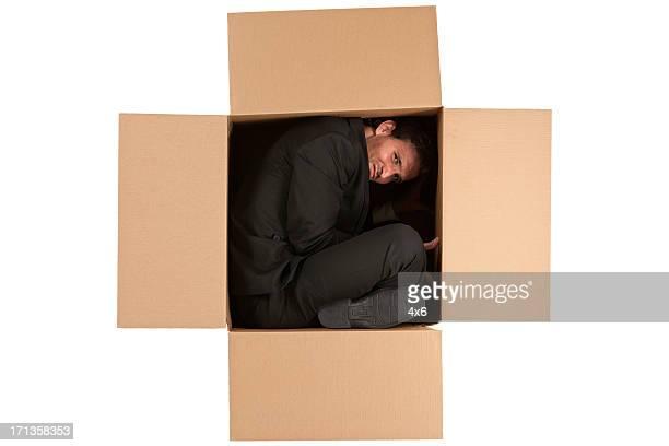 Empresario dentro de una caja de cartón
