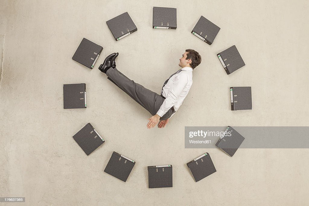 Businessman inside circle of files forming clock : Stock Photo