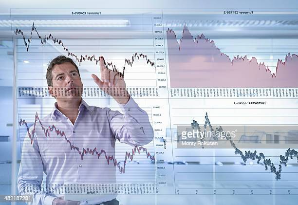 Businessman inspects graphs seen through interactive display
