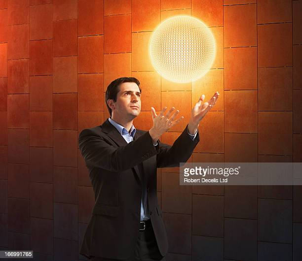 Businessman interacting with a sphere of energy