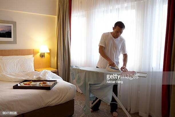 Businessman ironing shirt in hotel room