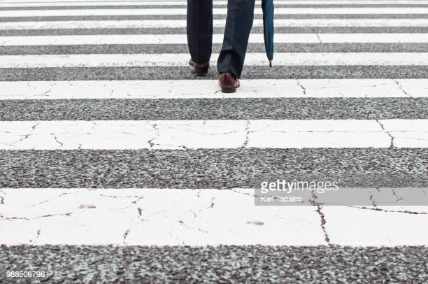 a businessman is crossing a zebra line - menswear stock pictures, royalty-free photos & images