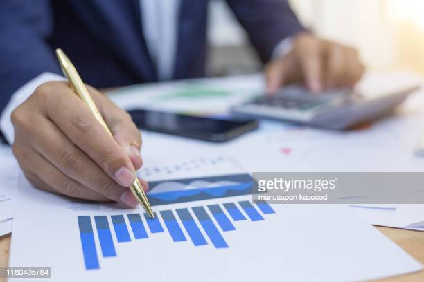 businessman is deeply reviewing a financial report for a return on investment or investment risk analysis. - charity benefit fotografías e imágenes de stock
