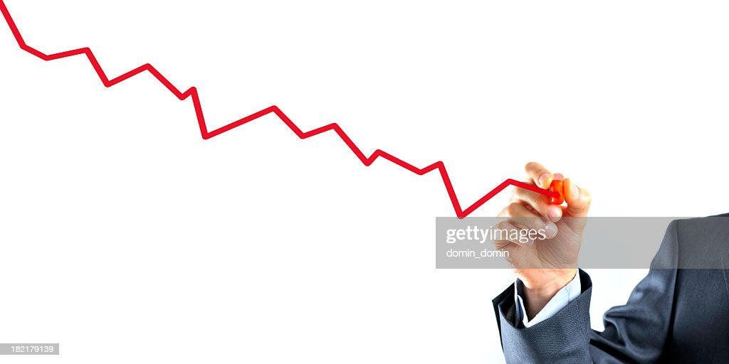 Businessman is drawing a graph with red line going down : Stock Photo