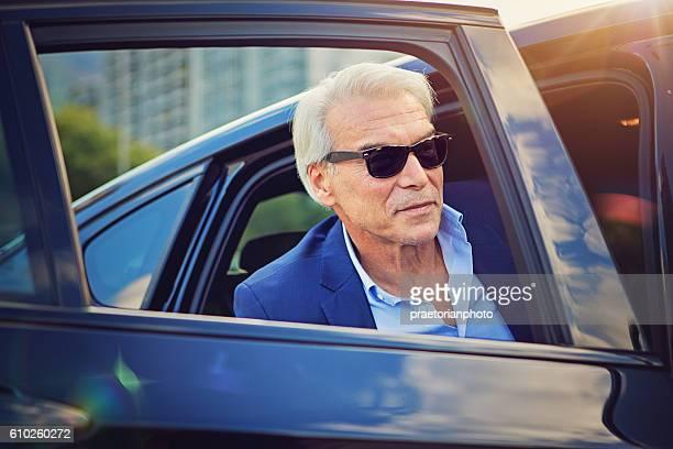 Businessman is enter/exit his car