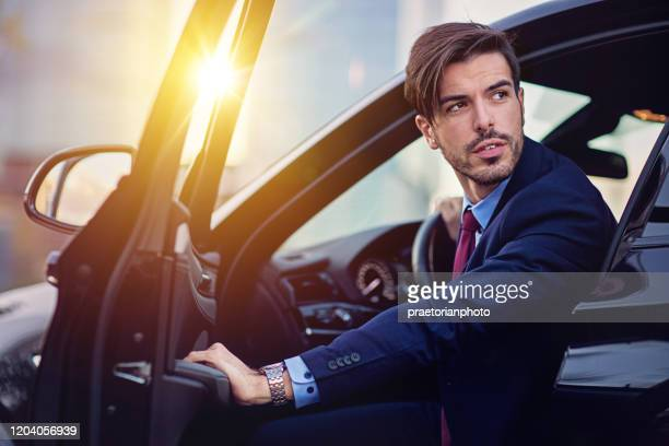 businessman is entering/exiting his car - entering stock pictures, royalty-free photos & images