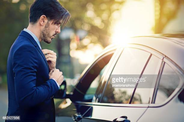 Businessman is fixing his necktie before a meeting