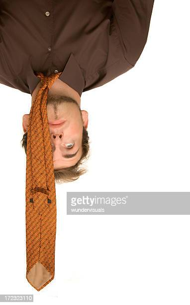 Businessman is hanging upside down having stress