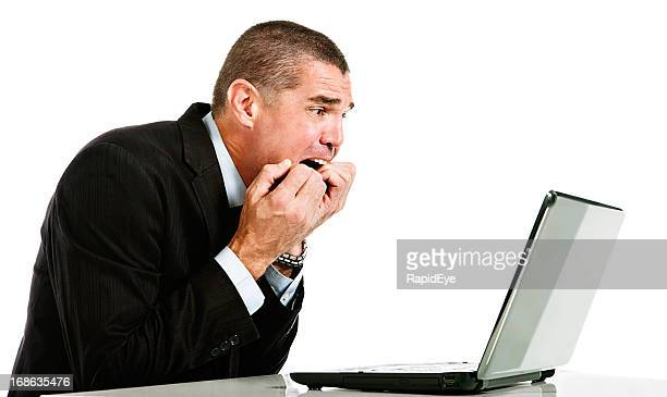 Businessman is horrified by something on laptop screen
