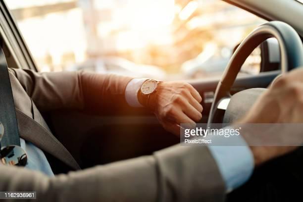 zakenman kijkt naar horloge in zijn auto - polshorloge stockfoto's en -beelden
