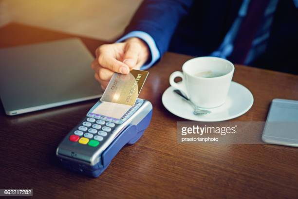 Businessman is paying in the cafeteria using his credit card