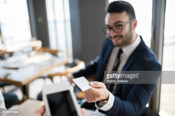 businessman is paying in the restaurant using his credit card - affari finanza e industria foto e immagini stock