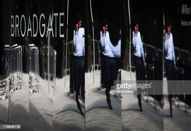 A businessman is reflected in the hoardings outside the construction site at No 5 Broadgate in London UK on Thursday Aug 15 2013 UBS AG Switzerland's...