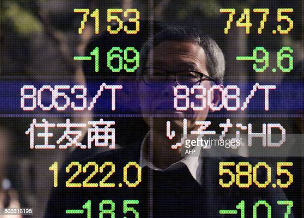 A businessman is reflected on a share prices board in Tokyo on January 4 2016 Tokyo stocks tumbled more than three percent on January 4 hit by weak...