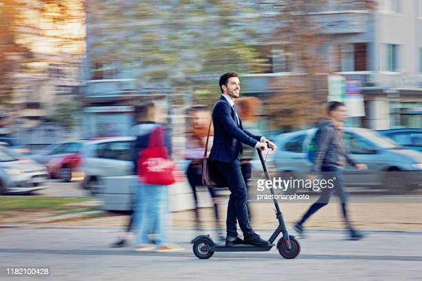 businessman is riding electric scooter in the city - electric scooter stock pictures, royalty-free photos & images