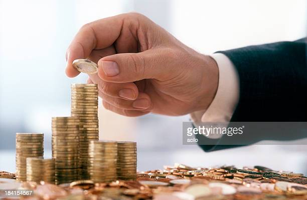 Businessman is stacking 1 Euro coins