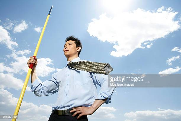 a businessman is standing with a javelin. - やり投げ ストックフォトと画像