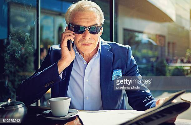 businessman is talking using his mobile phone - millionnaire stock photos and pictures