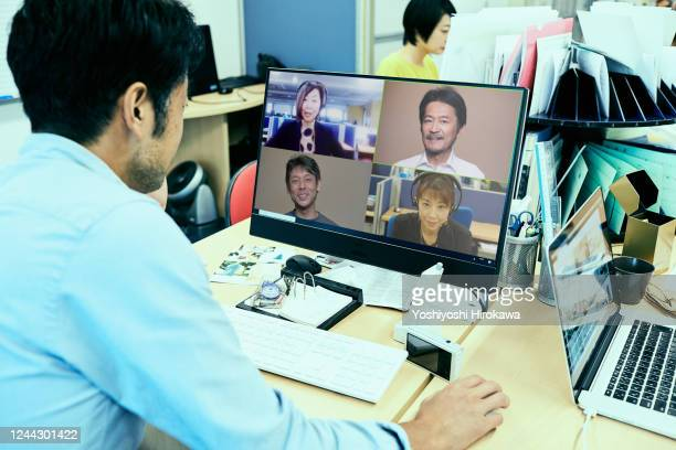 businessman is teleworking in small office - テレビ会議 ストックフォトと画像