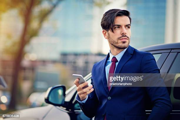 Businessman is texting next to his car