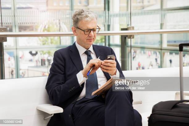 Businessman is using mobile phone while waiting in airport.