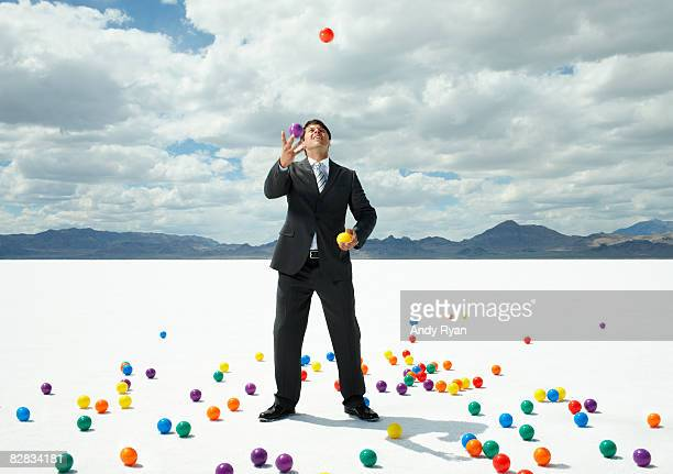 Businessman Juggling in Desert