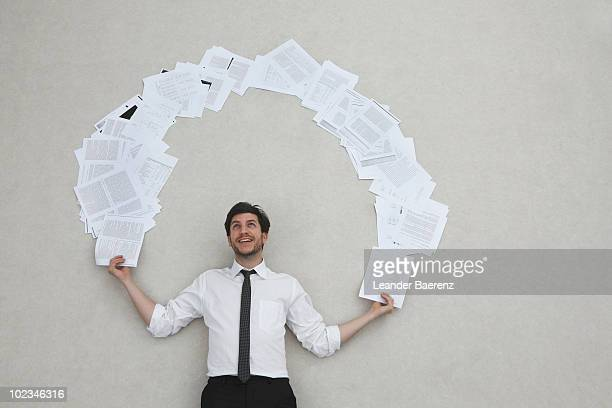 Businessman juggling with documents, smiling, portrait, elevated view
