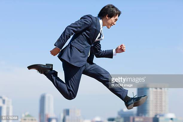 Businessman jumping, against cityscape, side view