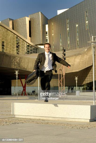 Businessman jumping bench in front of modern office building