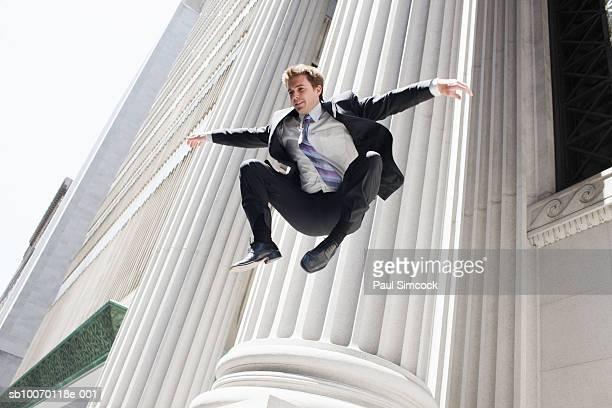 Businessman jumping by pillar