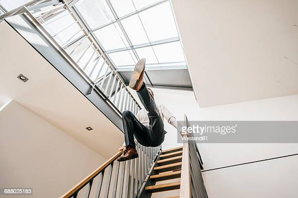 Businessman jumping down stairs