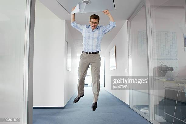 Businessman jumping for joy in office