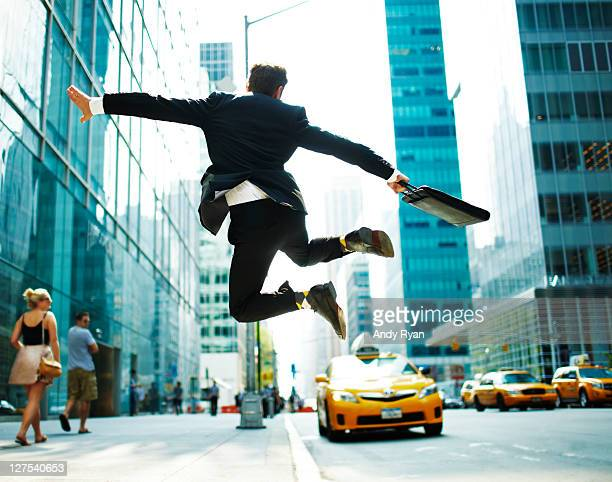 Businessman jumping for joy on city street.