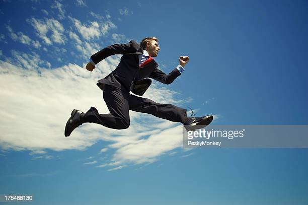 Businessman Jumping High Outdoors in Blue Sky with Clouds