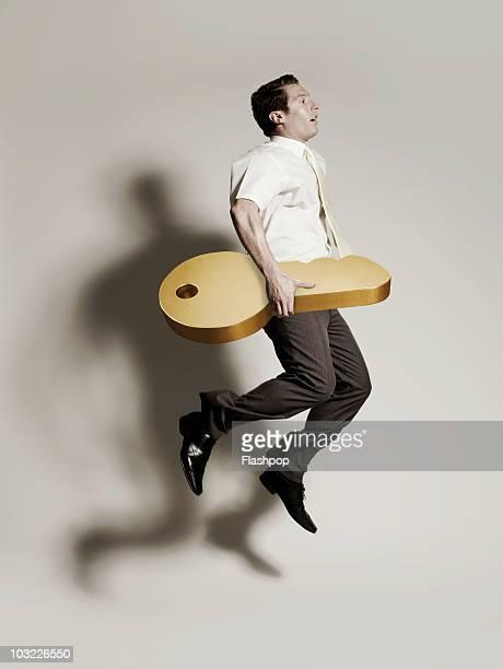 Businessman jumping holding large gold  key