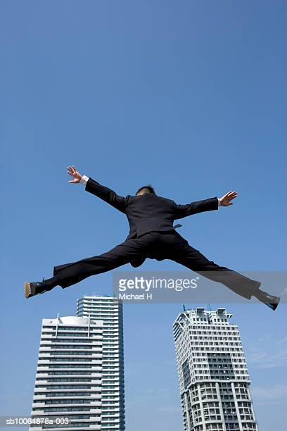 low angle view of man jumping from building against clear sky
