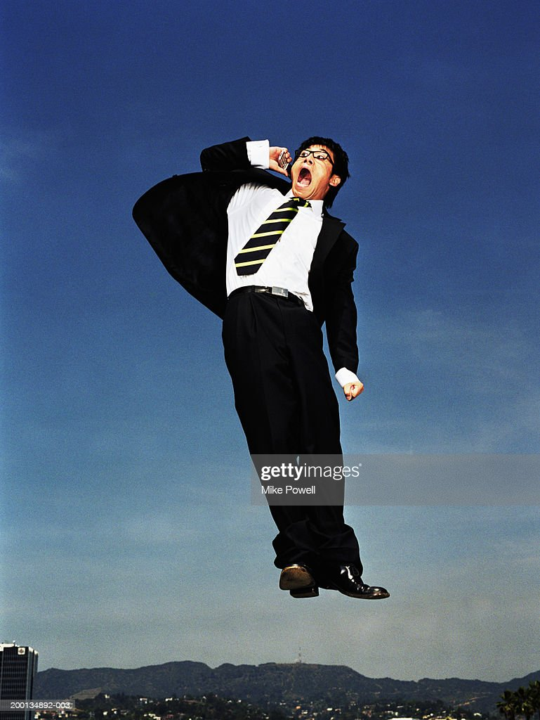 Businessman jumping in air, yelling into mobile phone, low angle : Stock Photo