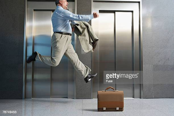 Businessman Jumping in Front of Elevator