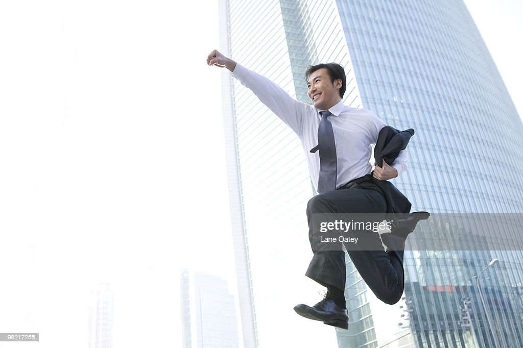 Businessman jumping in front of tall building : Stock Photo