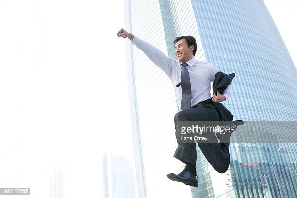 businessman jumping in front of tall building - skipping along stock pictures, royalty-free photos & images