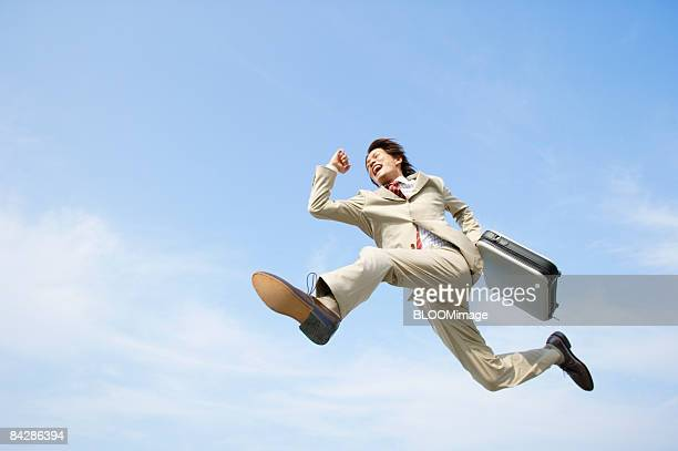 Businessman jumping in running pose, against blue sky