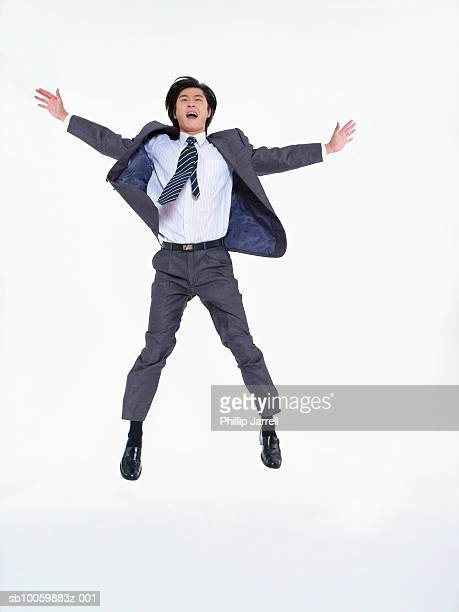 businessman jumping in studio - legs spread open stock photos and pictures